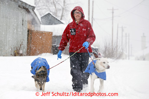 Mitch Seavey takes two of his dogs for a walk during his 24 hour break at the Takotna checkpoint just before dawn on Wednesday March 6, 2013. Iditarod Sled Dog Race 2013 Photo by Jeff Schultz copyright 2013 DO NOT REPRODUCE WITHOUT PERMISSION