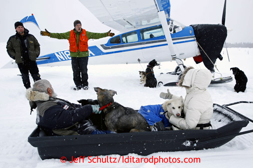 Pilot Greg Fischer, in orange vest, welcomes a sledload of dropped dogs at the airstrip in on Wednesday March 6, 2013. Iditarod Sled Dog Race 2013 Photo by Jeff Schultz copyright 2013 DO NOT REPRODUCE WITHOUT PERMISSION
