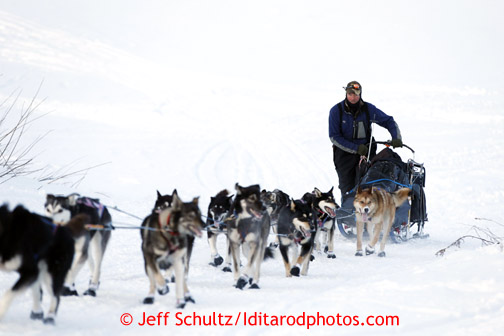 Sonny Lidner walks with his sled off the Yukon River and up the bank to the Kaltag checkpoint on Saturday March 9, 2013. Iditarod Sled Dog Race 2013 Photo by Jeff Schultz copyright 2013 DO NOT REPRODUCE WITHOUT PERMISSION