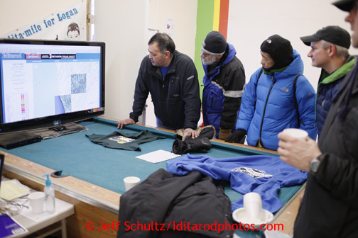 Unalakleet race fans watch the computer screen with musher's GPS positions at the Unalakleet checkpoint on Sunday March 10, 2013. Iditarod Sled Dog Race 2013 Photo by Jeff Schultz copyright 2013 DO NOT REPRODUCE WITHOUT PERMISSION