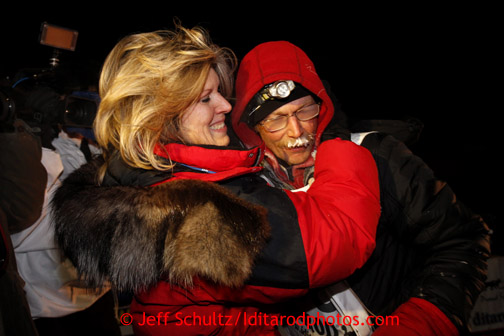 Mitch Seavey, right, 53, gets a hug and kiss from his wife, Janine, after pulling into Nome first and winning his second Iditarod sled dog race on Tuesday March 12, 2013. Seavey made the journey from Willow in 9 days, 7 hours, 39 minutes, 56 seconds.  Iditarod Sled Dog Race 2013 Photo by Jeff Schultz copyright 2013 DO NOT REPRODUCE WITHOUT PERMISSION