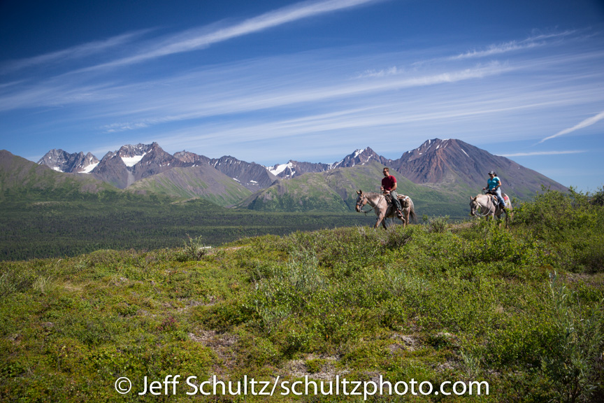 Visitors on horseback trail ride out of The Perrin's Rainy Pass Lodge with the Alaska Range background  Southcentral, Alaska