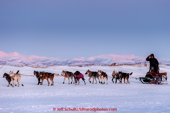 Aaron Burmeister runs on the slough with the Whaleback Mountains in the background leaving the Unalakleet  checkpoint at sunset on Sunday  March 15, 2015 during Iditarod 2015.   (C) Jeff Schultz/SchultzPhoto.com - ALL RIGHTS RESERVED  DUPLICATION  PROHIBITED  WITHOUT  PERMISSION