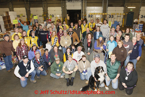 "Friday, February 15, 2013.   Some 60+ Iditarod volunteers pose for a group photo during the ""people food"" drop at Airland Transport in Anchorage.  Each of the 22 checkpoints gets an assortment of food to be eaten by the checkpoint volunteers such as checkers, veterinarians, pilots, communications people and more."