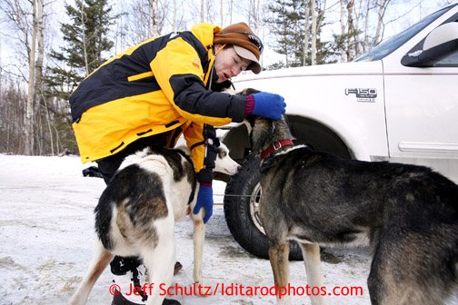 Volunteer veterinarian Carol Hedges of east Texas checks Charley Bejna's dog Poncho in Wasilla Wednesday, Feb. 27, 2013.