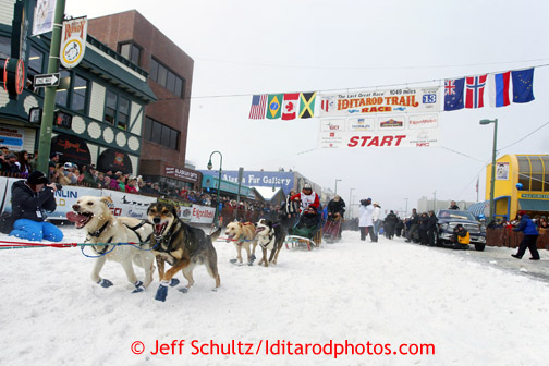 Jason Mackey runs down the chute on 4th avenue during ceremonial start of the Iditarod sled dog race Anchorage Saturday, March 2, 2013.  Photo (C) Jeff Schultz/IditarodPhotos.com  Do not reproduce without permission
