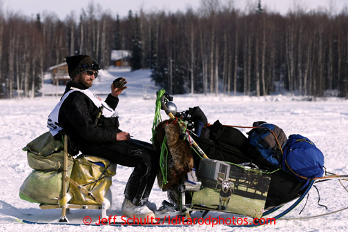 Nicolas Petit sits on his sled on Long Lake after leaving the re-start line of the Iditarod sled dog race in Willow, Alaska Sunday, March 3, 2013.