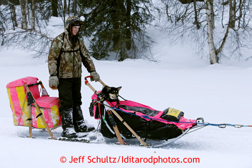 Wade Marrs of Wasilla brings his dog Pumpkin into the Finger Lake checkpoint in the sled March 4, 2013.