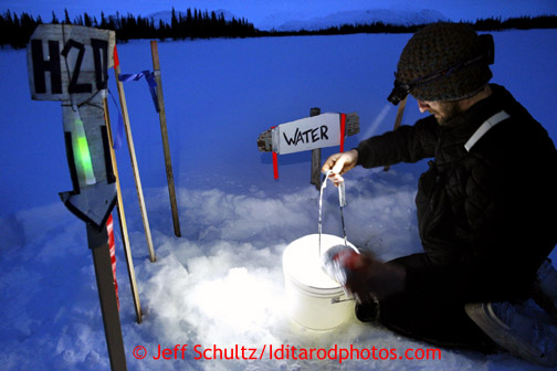 Nicolas Petit of Girdwood gets water from the hole in Finger Lake at the checkpoint Monday, March 4, 2013.