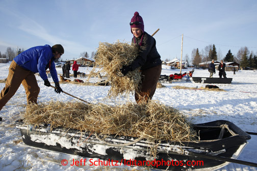Trail helpers Kara Wortley, right, and Micah Rydman clean up straw at the Nikolai checkpoint March 5, 2013.