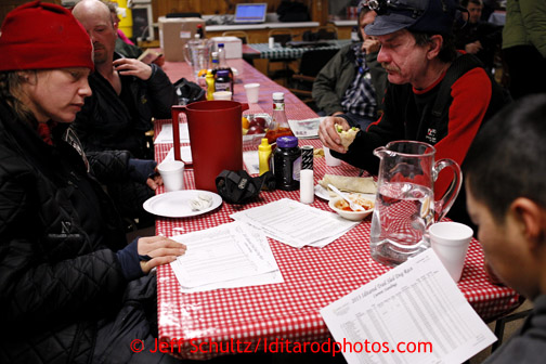 With the race standings in hand, Aliy Zirkle, Aaron Burmeister, Allen Moore and Mike Williams Jr. talk race strategy at the Takotna checkpoint during their 24 hour layover on Wednesday March 6, 2013. Iditarod Sled Dog Race 2013 Photo by Jeff Schultz copyright 2013 DO NOT REPRODUCE WITHOUT PERMISSION