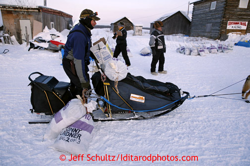Sonny Lidner grabs his dog food bags after checking in at the Kaltag checkpoint on Saturday March 9, 2013. Iditarod Sled Dog Race 2013 Photo by Jeff Schultz copyright 2013 DO NOT REPRODUCE WITHOUT PERMISSION