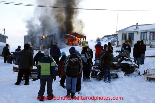 People watch as firefighters try to put out a house fire in the village of Elim on Monday March 11, 2013. Iditarod Sled Dog Race 2013 Photo by Jeff Schultz copyright 2013 DO NOT REPRODUCE WITHOUT PERMISSION
