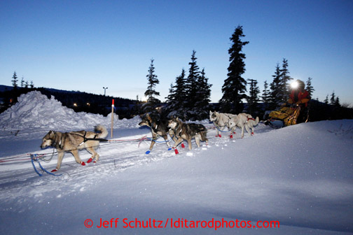 Mitch Seavey heads out of the Elim checkpoint with his headlamp on at dusk on Monday March 11, 2013. Iditarod Sled Dog Race 2013 Photo by Jeff Schultz copyright 2013 DO NOT REPRODUCE WITHOUT PERMISSION