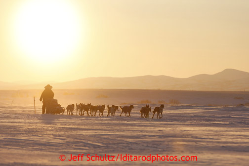 Kelley Griffin runs on the trail at sunrise as she gets closer to the Unalakleet checkpoint on Monday morning March 11, 2013. Iditarod Sled Dog Race 2013 Photo by Jeff Schultz copyright 2013 DO NOT REPRODUCE WITHOUT PERMISSION