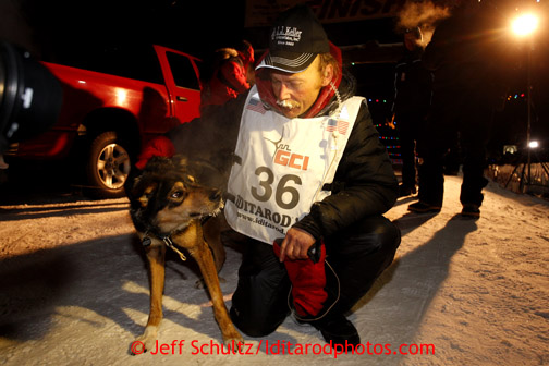 Mitch Seavey, right, 53, pets one of his lead dogs, Tanner, after pulling into Nome first and winning his second Iditarod sled dog race on Tuesday March 12, 2013. Seavey made the journey from Willow in 9 days, 7 hours, 39 minutes, 56 seconds.  Iditarod Sled Dog Race 2013 Photo by Jeff Schultz copyright 2013 DO NOT REPRODUCE WITHOUT PERMISSION