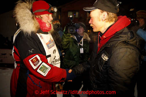 Aily Zirkle, left, shakes hands with Iditarod winner Mitch Seavey after she pulled into Nome minutes after him on Tuesday March 12, 2013. Iditarod Sled Dog Race 2013 Photo by Jeff Schultz copyright 2013 DO NOT REPRODUCE WITHOUT PERMISSION