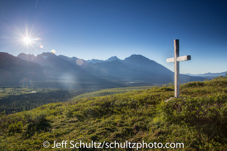 A cross ( Christian symbol ) sits on knoll in valley in Alaska Range