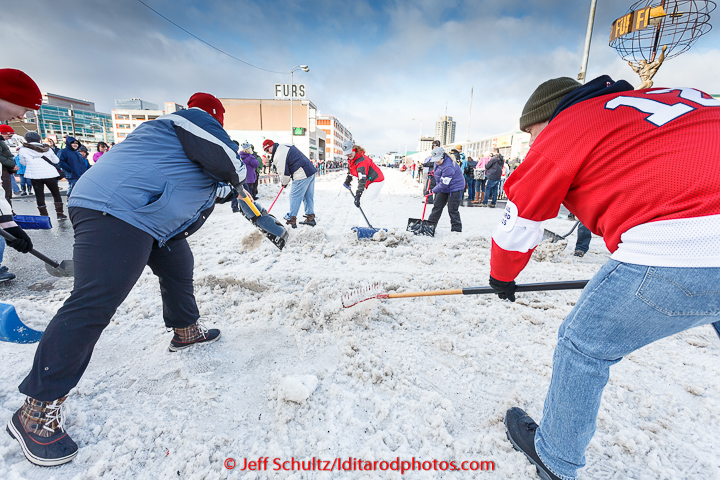 Volunteers shovels snow back onto the trail at a street crossing on 4th avenue during the cermonial start day of Iditarod 2015 in Anchorage, Alaska. Saturday March 7, 2015 (C) Jeff Schultz/SchultzPhoto.com - ALL RIGHTS RESERVED  DUPLICATION  PROHIBITED  WITHOUT  PERMISSION