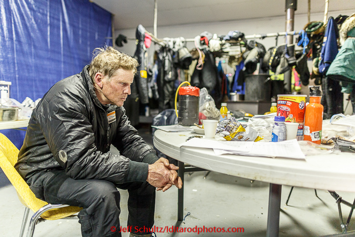 Lachlan Clarke has the 1,000 - mile stare as he rests in the community center as musher gear dries in the backgroud at the Tanana checkpoint on Wednesday morning  March 11th during the 2015 Iditarod. (C) Jeff Schultz/SchultzPhoto.com - ALL RIGHTS RESERVED  DUPLICATION  PROHIBITED  WITHOUT  PERMISSION