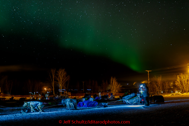 Teams rest on the baseball field as the Northern Lights play overhead in the morning at the Huslia checkpoint on Saturday  March 14, 2015 during Iditarod 2015.   (C) Jeff Schultz/SchultzPhoto.com - ALL RIGHTS RESERVED  DUPLICATION  PROHIBITED  WITHOUT  PERMISSION