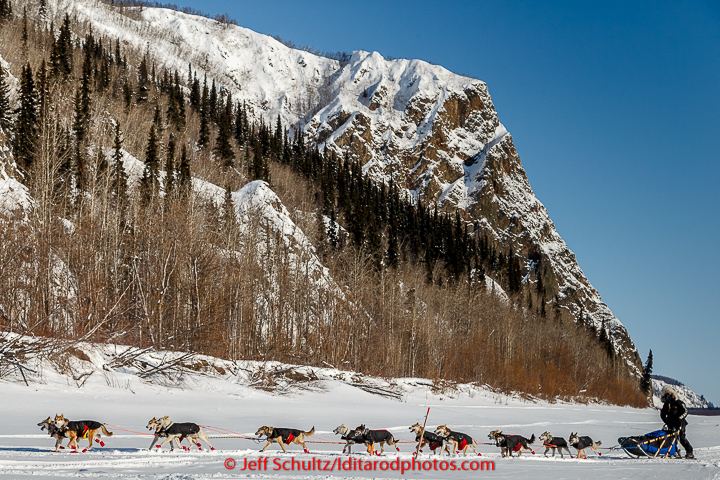 Kristy Berington runs past cliffs and Koyukuk Mountains just priort to the Koyukuk checkpoint on the afternoon of Sunday  March 15, 2015 during Iditarod 2015.   (C) Jeff Schultz/SchultzPhoto.com - ALL RIGHTS RESERVED  DUPLICATION  PROHIBITED  WITHOUT  PERMISSION