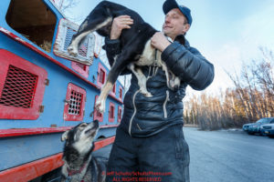 Iditarod musher Charlie Benja takes out a dog from the dog box at the 2016 Iditarod Pre-race vet check in Wasilla, Alaska. March 02, 2016 © Jeff Schultz/SchultzPhoto.com ALL RIGHTS RESERVED DO NOT REPRODUCE WITHOUT PERMISSION