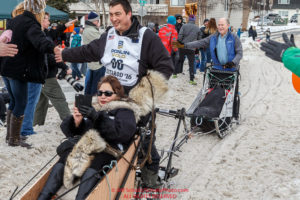 Governor Walker rides the tag-sled of John Baker past spectators on Cordova Street during the Ceremonial Start of the 2016 Iditarod in Anchorage, Alaska.  March 05, 2016