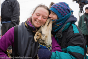 18 year old Melissa Owens of Nome gets a hug from her mom Pat and a kiss from her lead dog Yoda after finishing in 30th place during the 2008 Iditarod