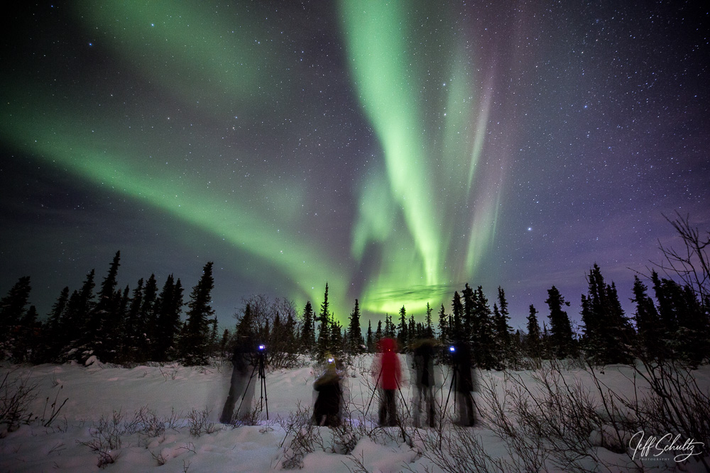 Participants on a Private custom winter night-sky and landscape photography tour view the Northern Lights / Aurora over Cleary summit area north of Fairbanks, AK .