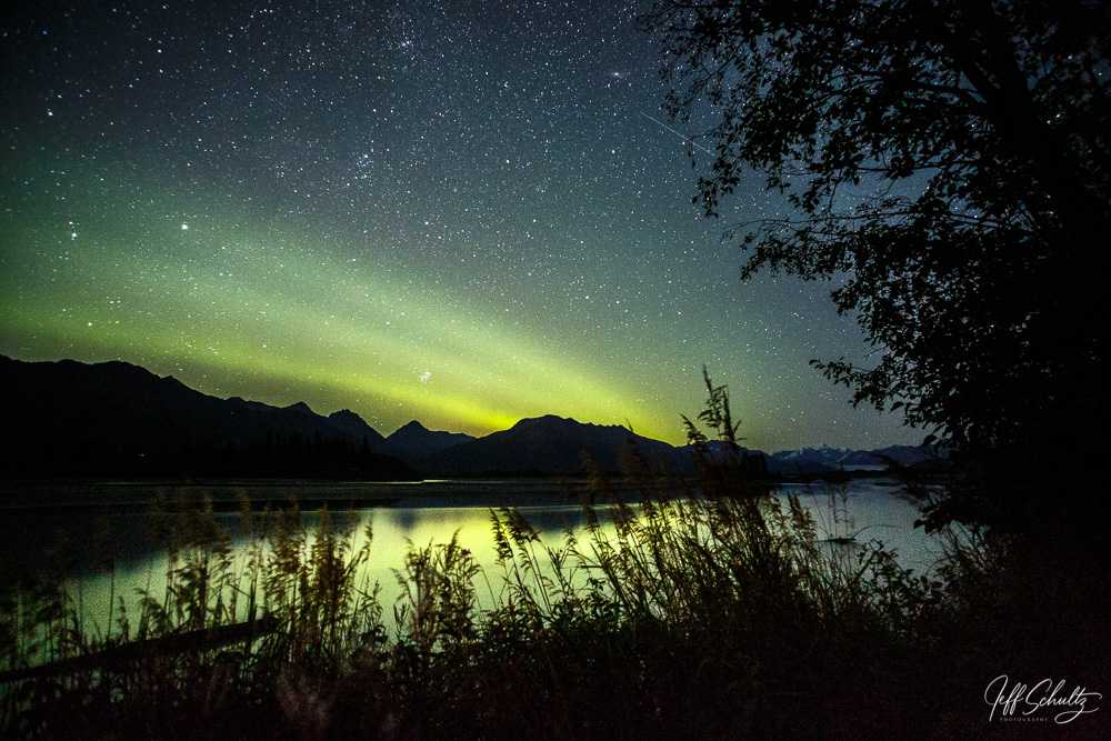 Fall landscape of the Northern Lights (Aurora Borealis) appearing in the night sky with stars reflecting in Knik River with the Chugach Mountains in the background. Matanuska Valley, near Palmer Alaska Southcentral.